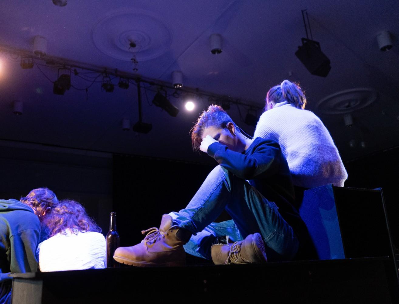 Sittende skuespiller på scene under musikalen Alene Sammen.