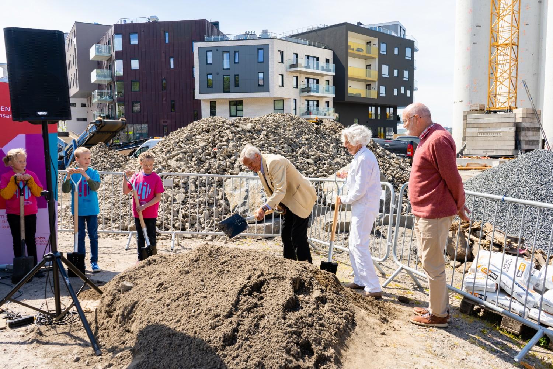 Personer tar spadetak på byggeplass