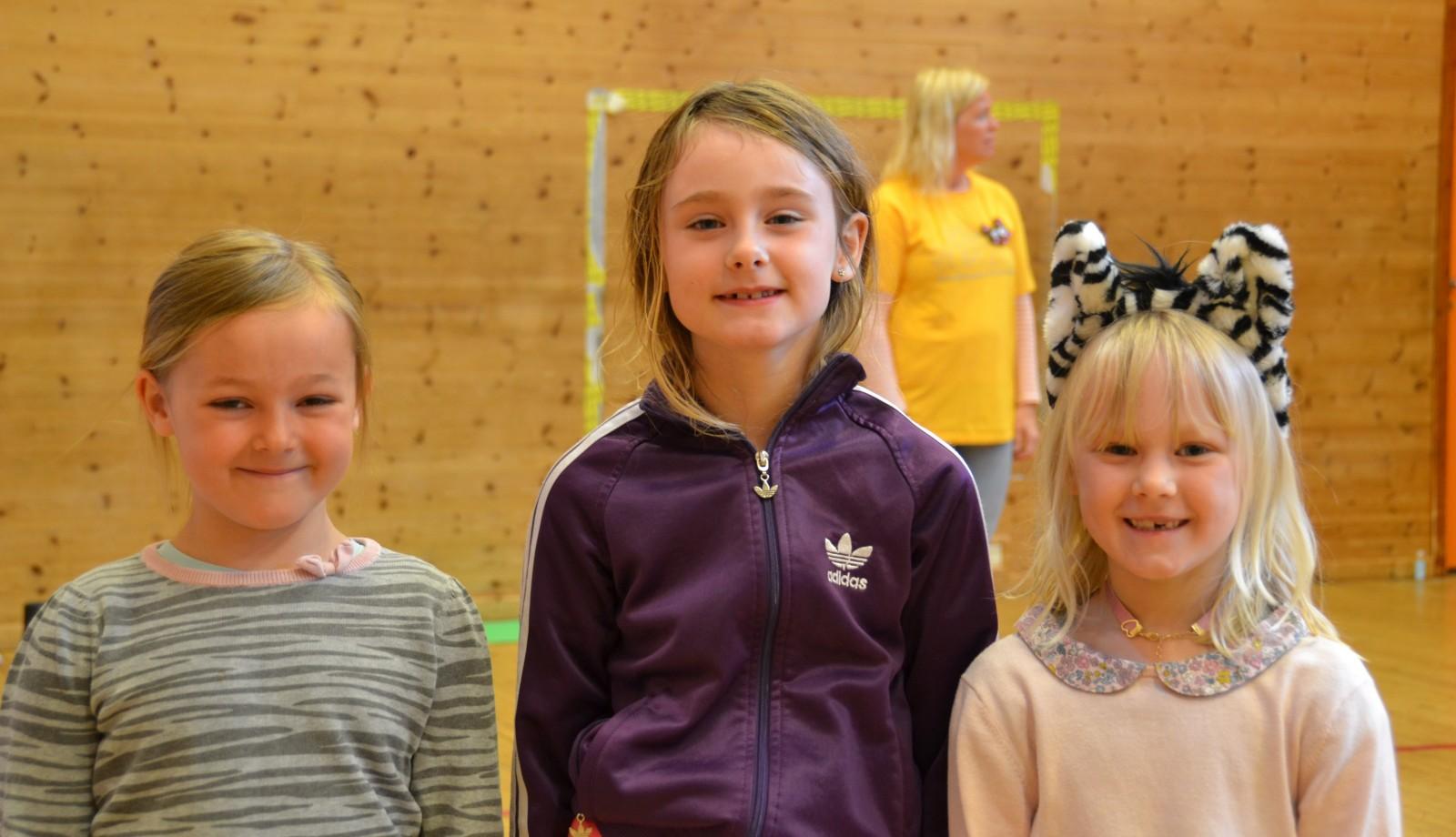 Tre jenter smiler mot kamera