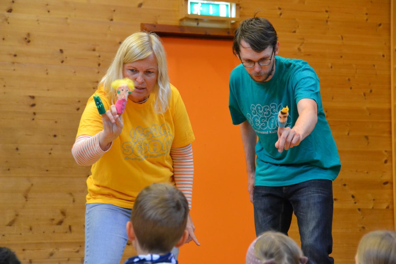 To personer viser frem fingerdukker til barn