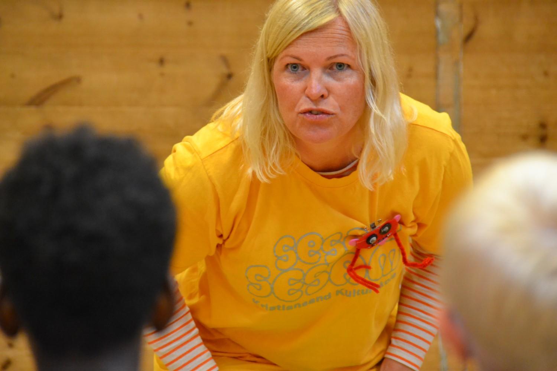 Dame i gul t-skjorte sitter fremoverlent og lytter til en elev