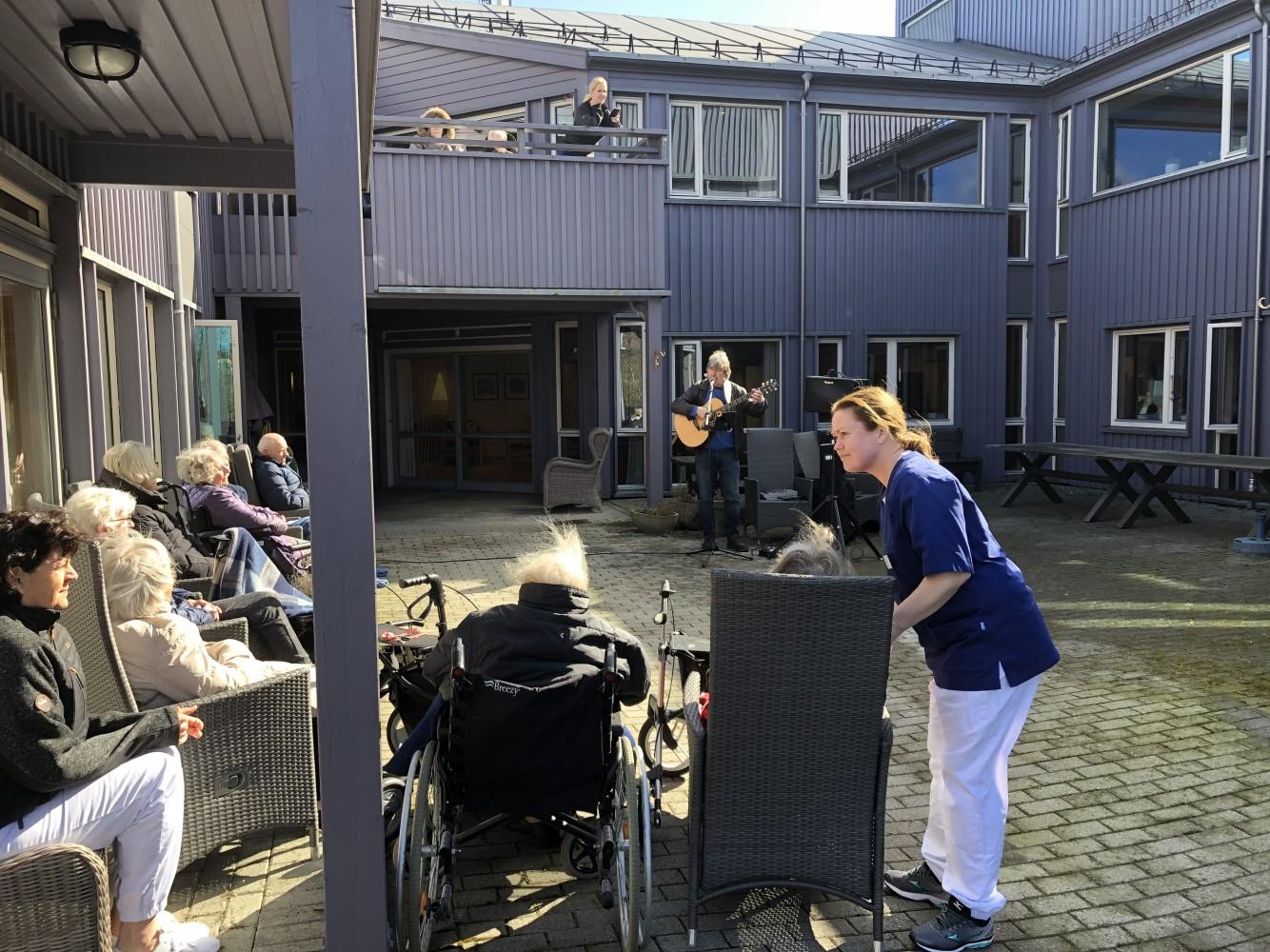 Mann står ute og spiller musikk i en bakgård. Mange eldre beboere er publikum.
