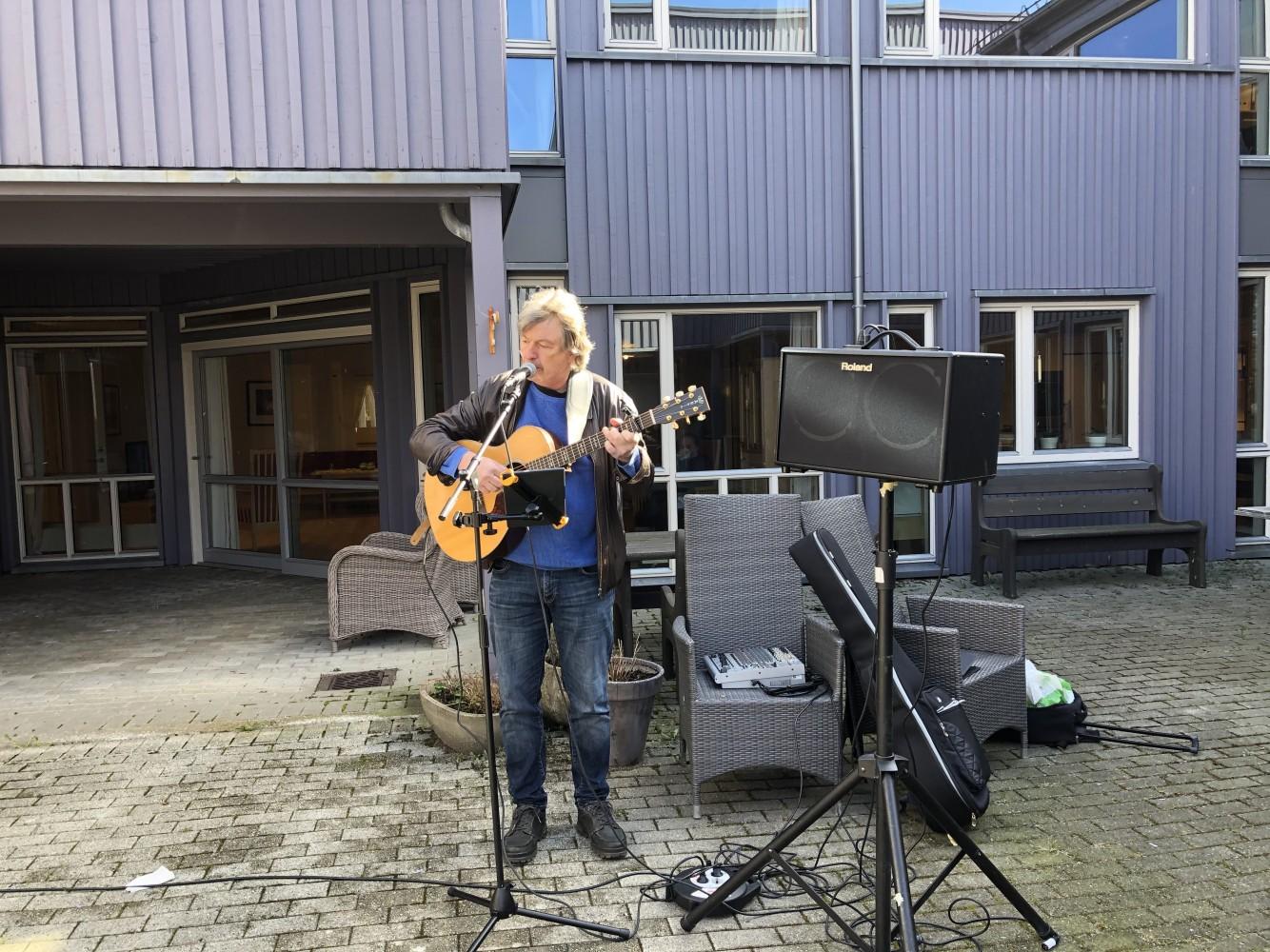 Mann står ute og spiller musikk i en bakgård