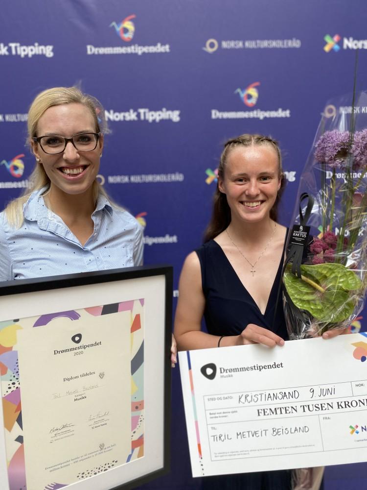 To personer smilende med diplom og sjekk foran Norsk Tipping-vegg