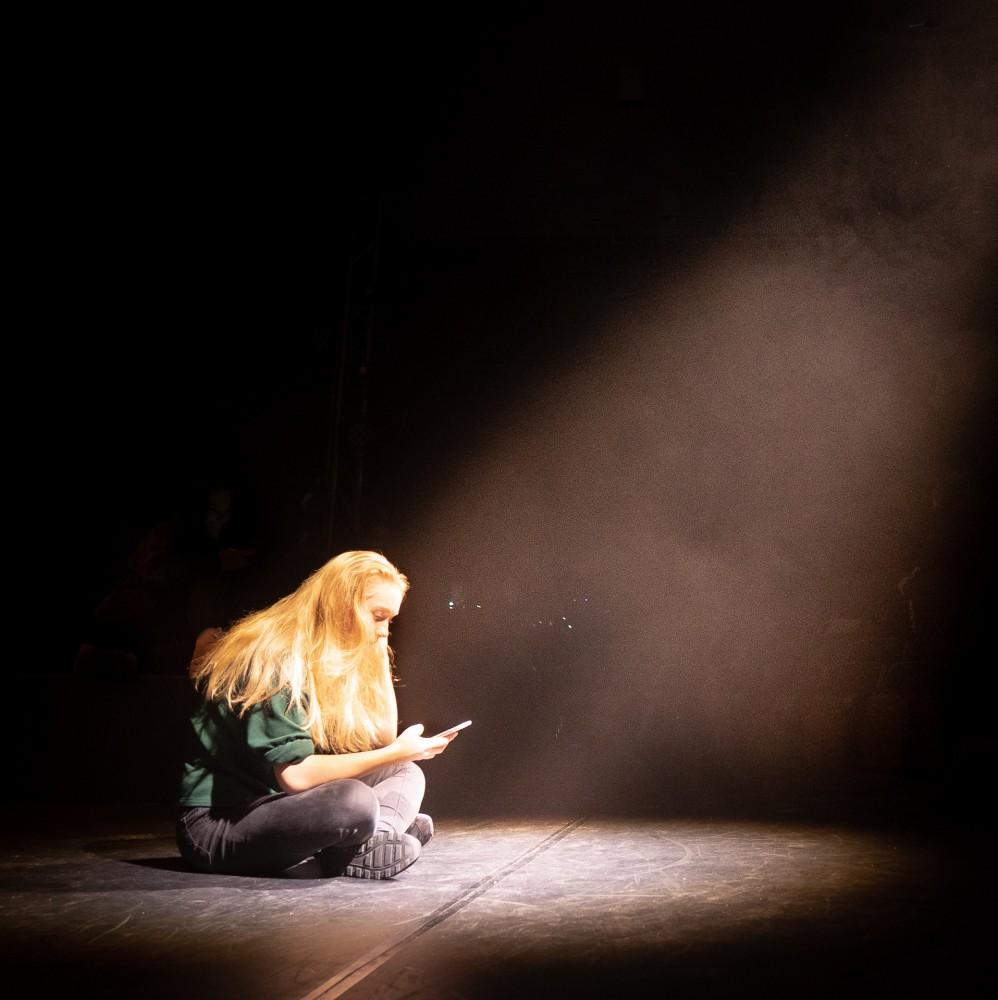 Karakteren Elise sitter på scenen under musikalen Alene Sammen.