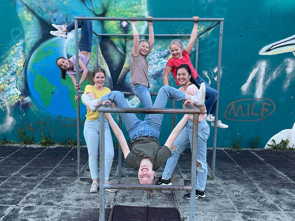 Danseelever henger og står i klatrestativ. Foto.
