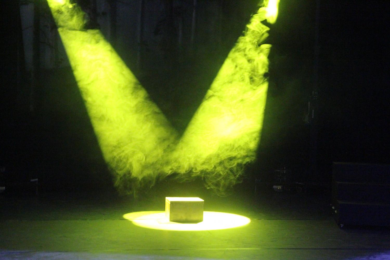 En boks på en scene, opplyst av to skinnende, grønne lys. Foto.