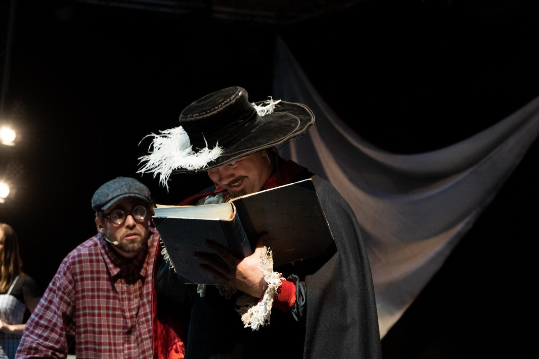 To personer på scenen som leser i en bok i spenning. Foto.