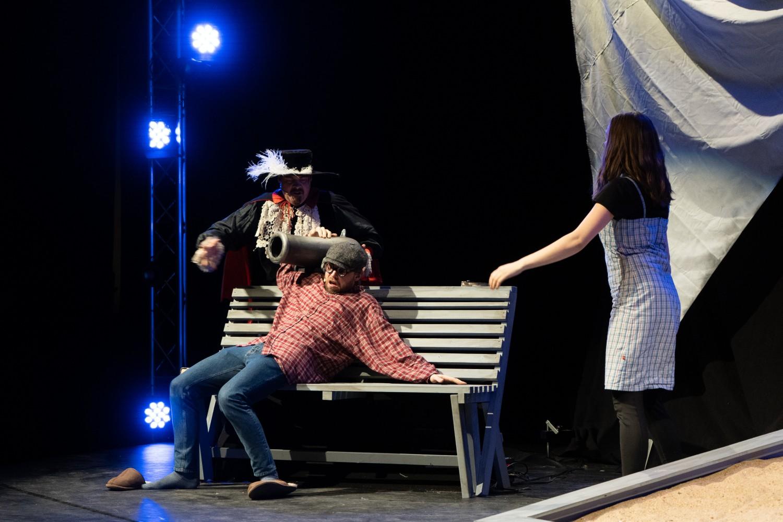 Tre personer på scenen, hvor den ene bærer en kanon på skulderen. Foto.
