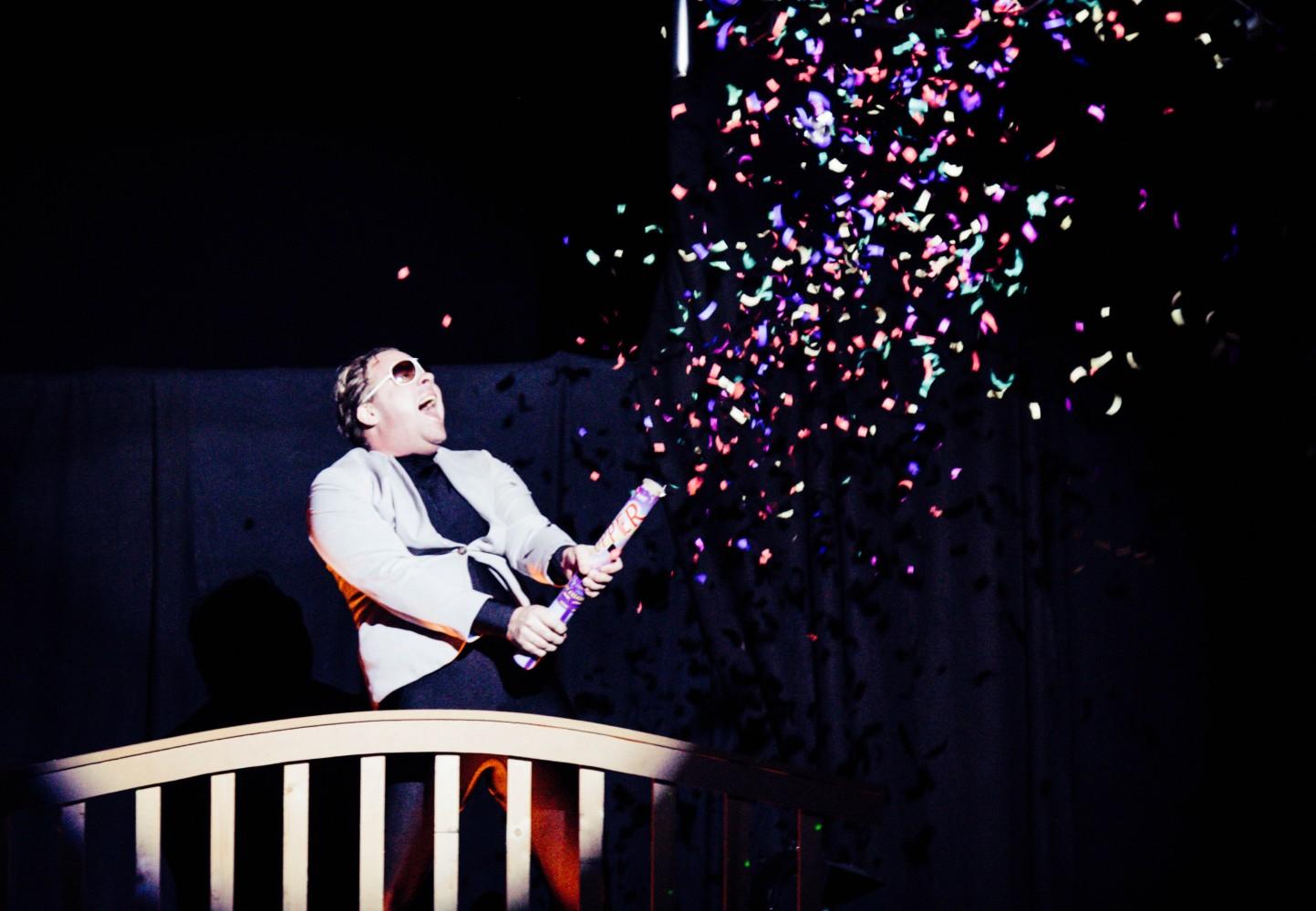 En person på scenen som skyter opp konfetti. Foto.