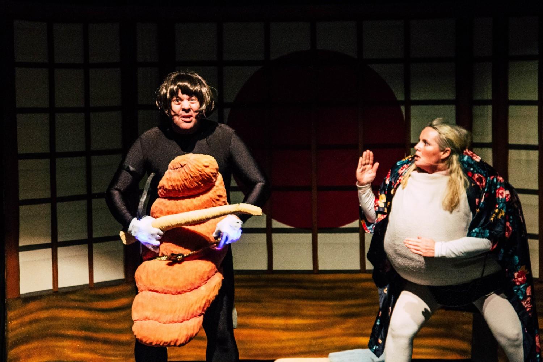 To personer på scenen, den ene kledd ut som en sushi, og den andre en kompe. Foto.