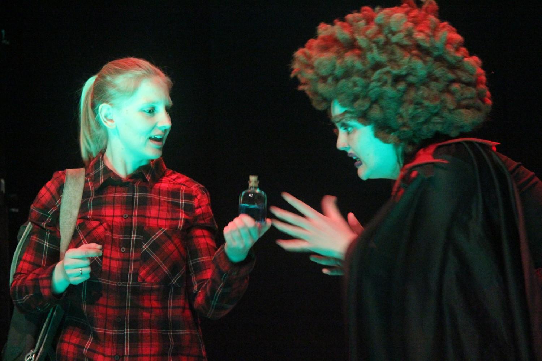 To personer på scenen, en kledd ut som en heks. Foto.