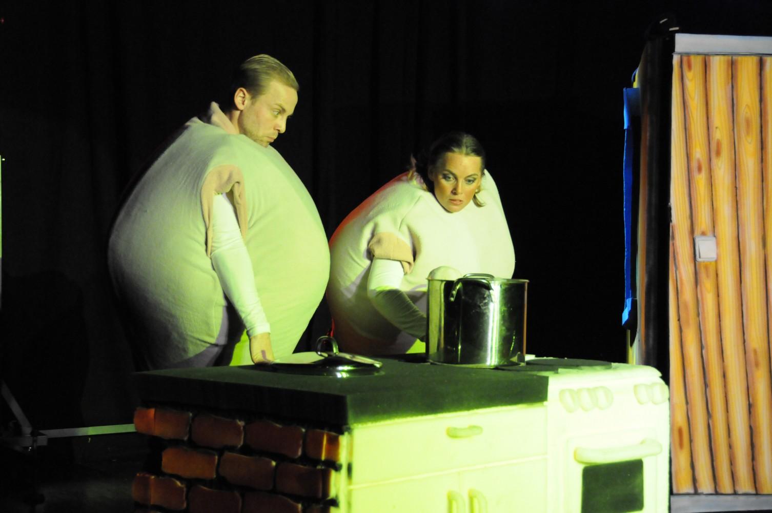 To personer på scenen i kledd som komper, foran et kjøkken. Foto.