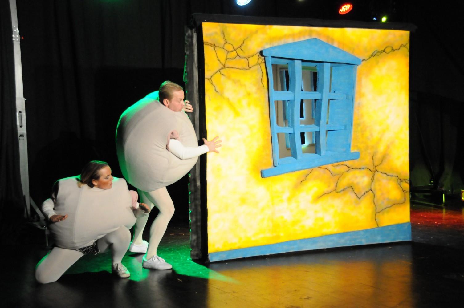 To personer på scenen i kledd som komper, som lister seg ved et vindu. Foto.