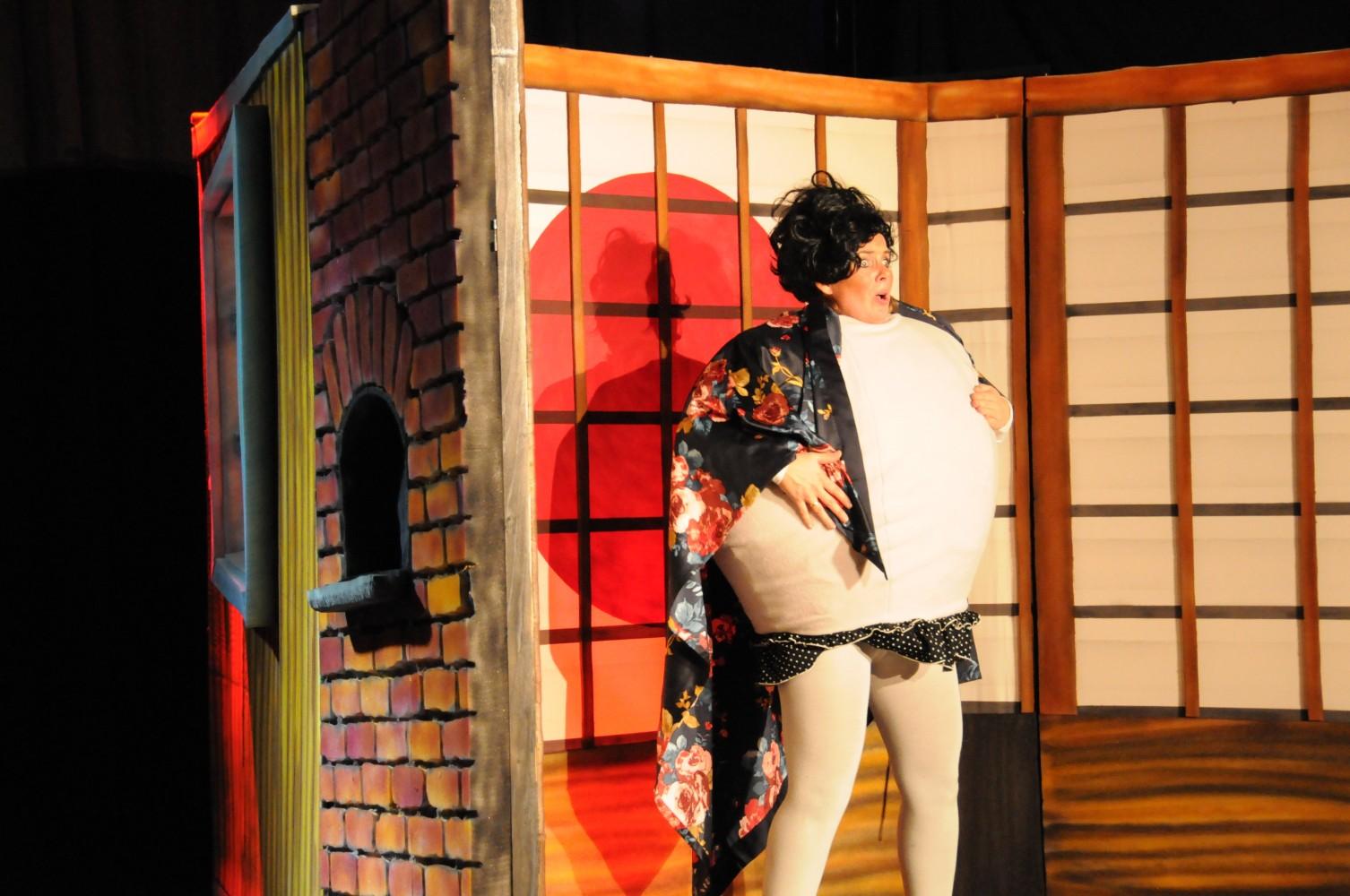 En person kledd ut som en kompe, i en Asiatisk setting. Foto.