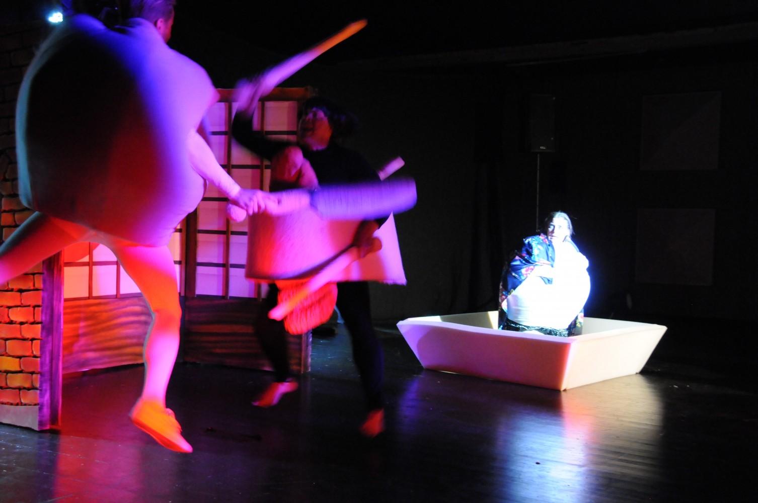 Tre personen på scenen i kostyme. To karakterer som er i kamp, og en som sitter spent å ser på. Foto.