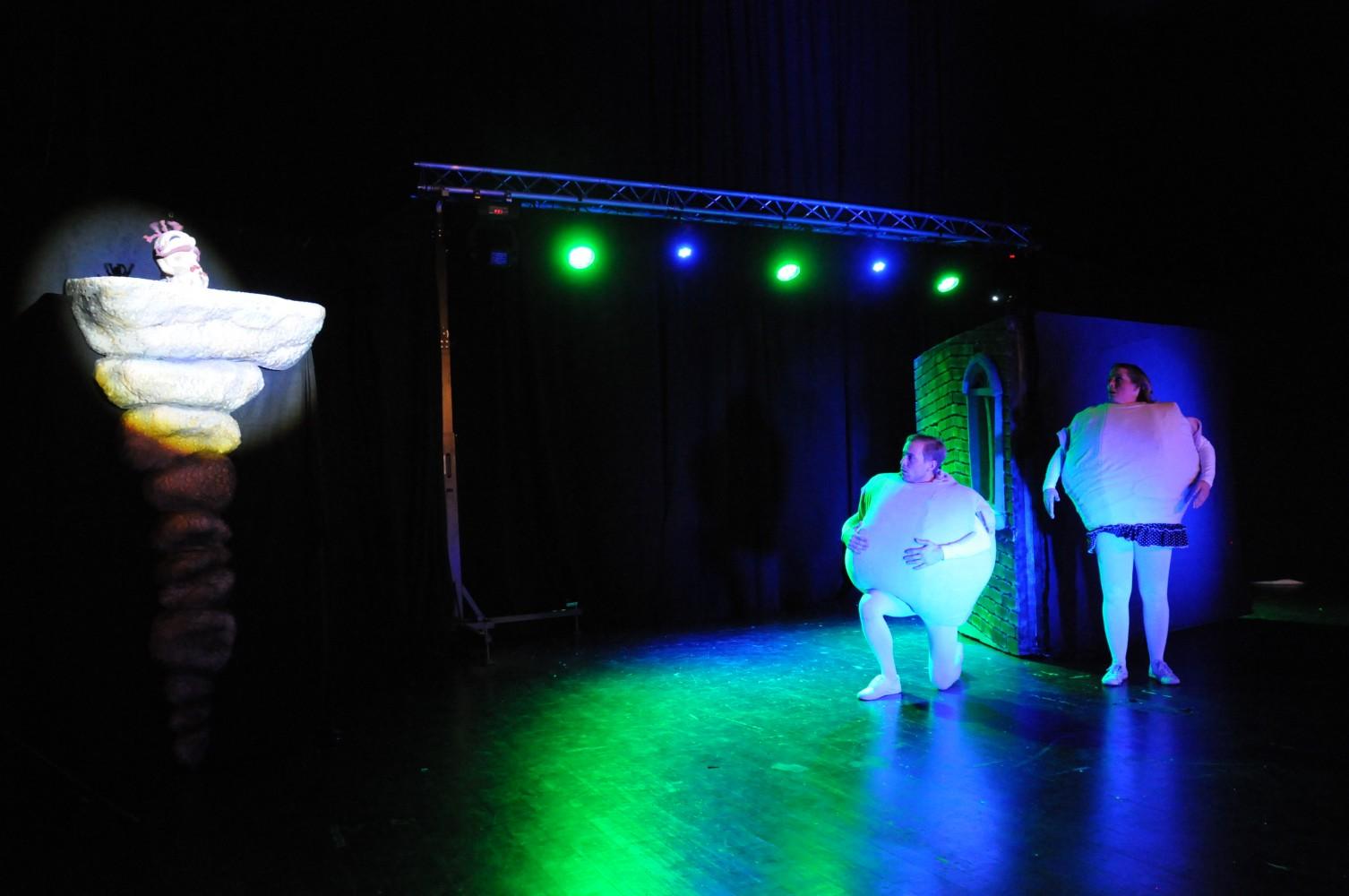 To personer på scenen i kledd som komper, og en dukke.