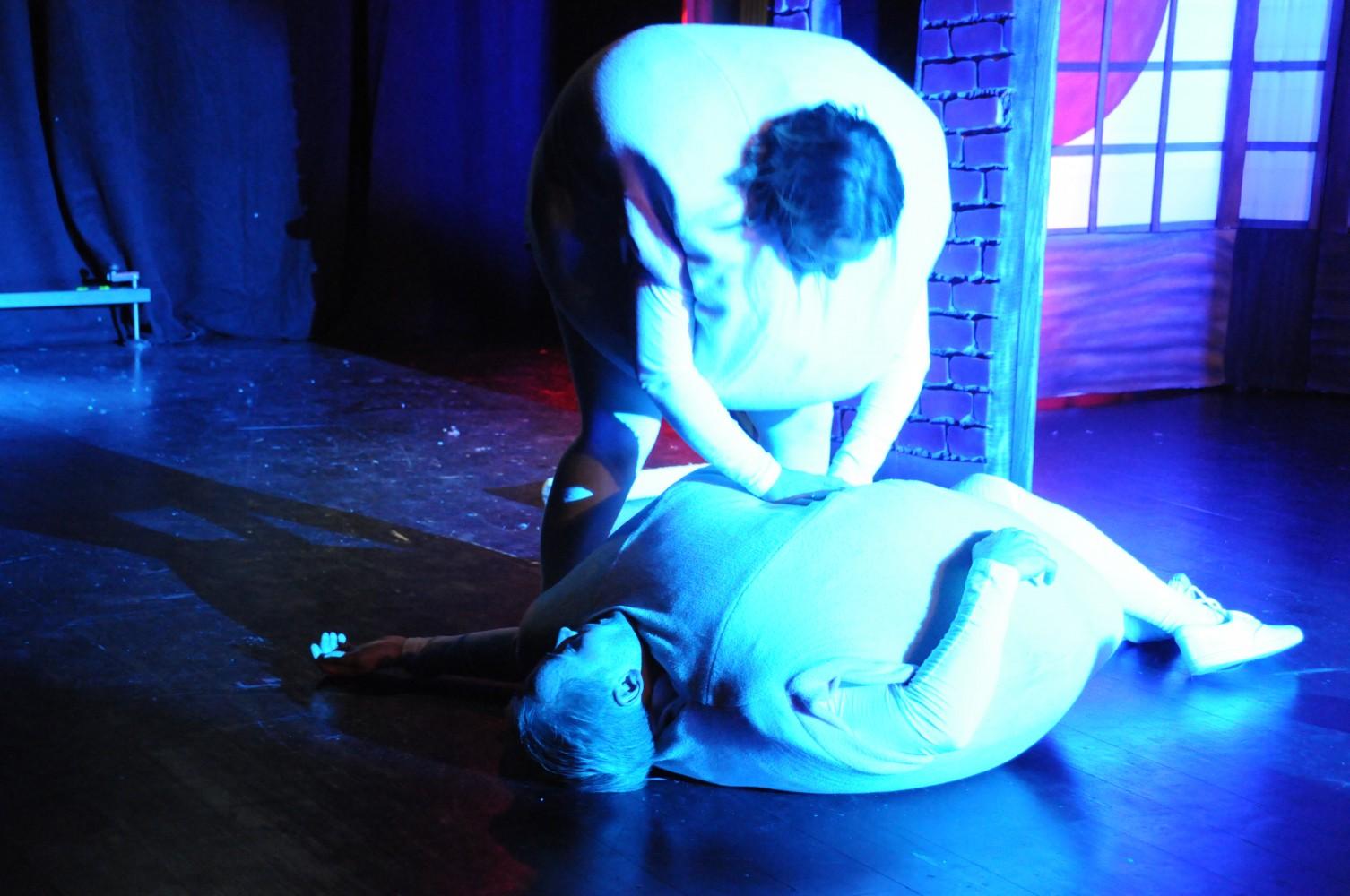 To personer på scenen kledd ut som komper. Den ene kompen prøver å redde den andre som ligger på bakken. Foto.