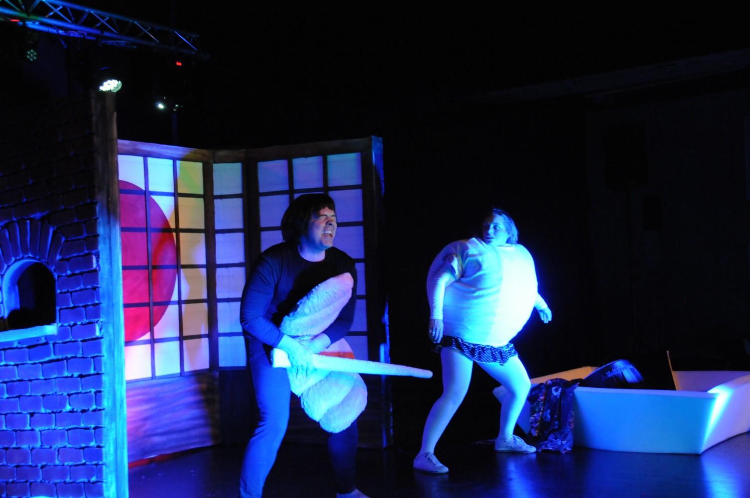 To personer på scenen i kostyme som ser bekymret ut. Foto.