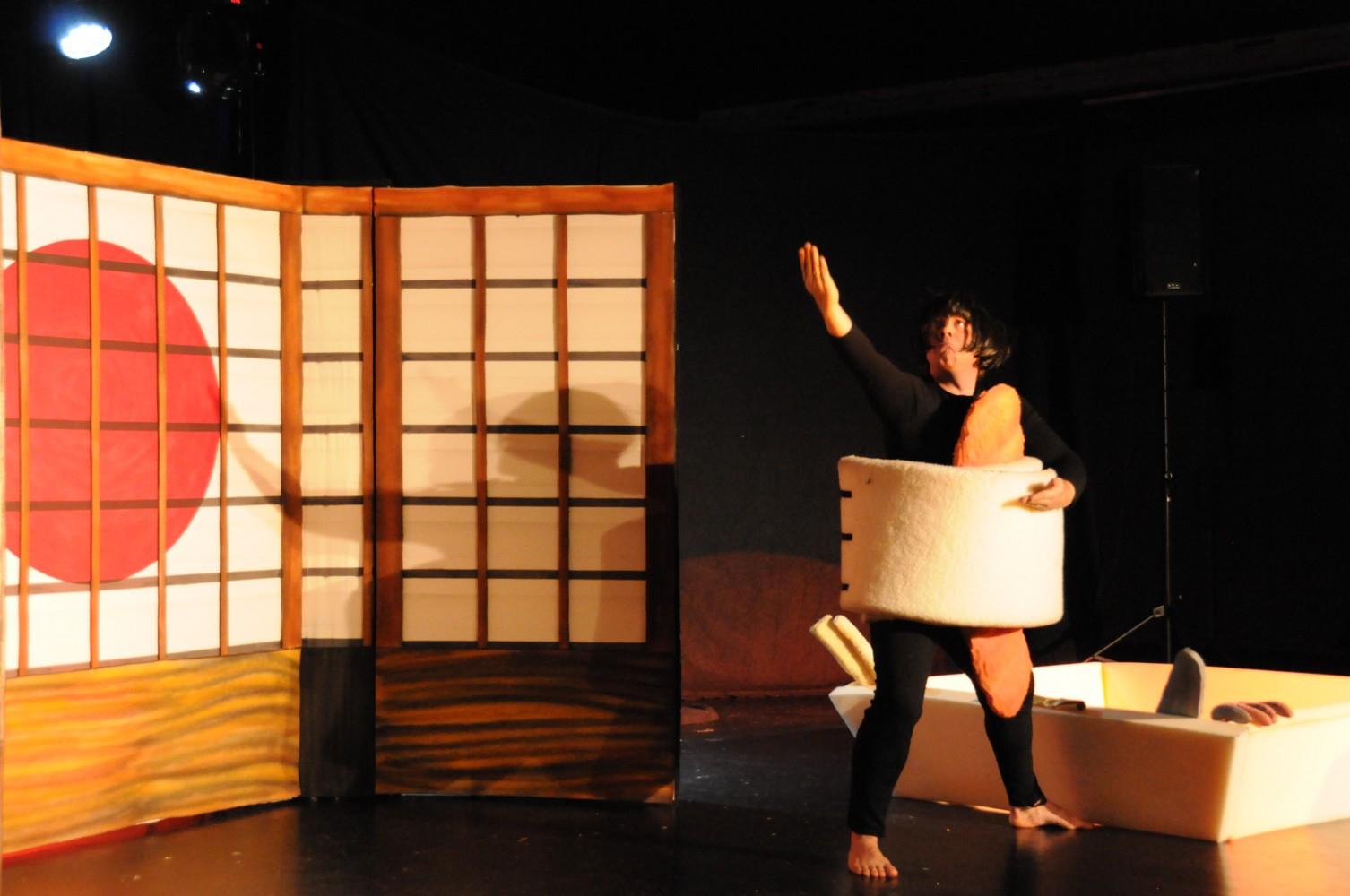 En personen på scenen i kledd som en sushi, i en asiatisk setting. Foto.