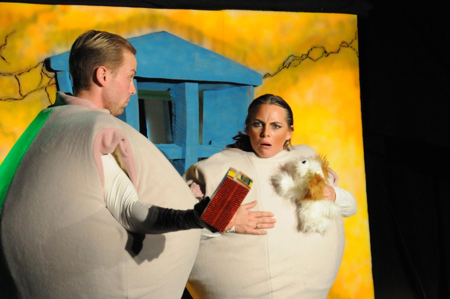 To personer på scenen i kledd som komper, i undring av en boks. Foto.