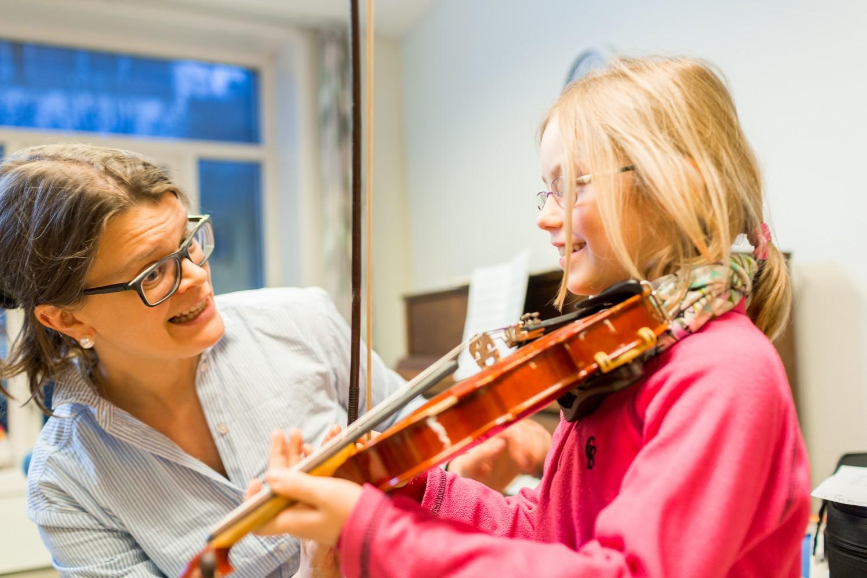 Nærbilde av en elev som spiller fiolin, og lærer som hjelper til. Foto.