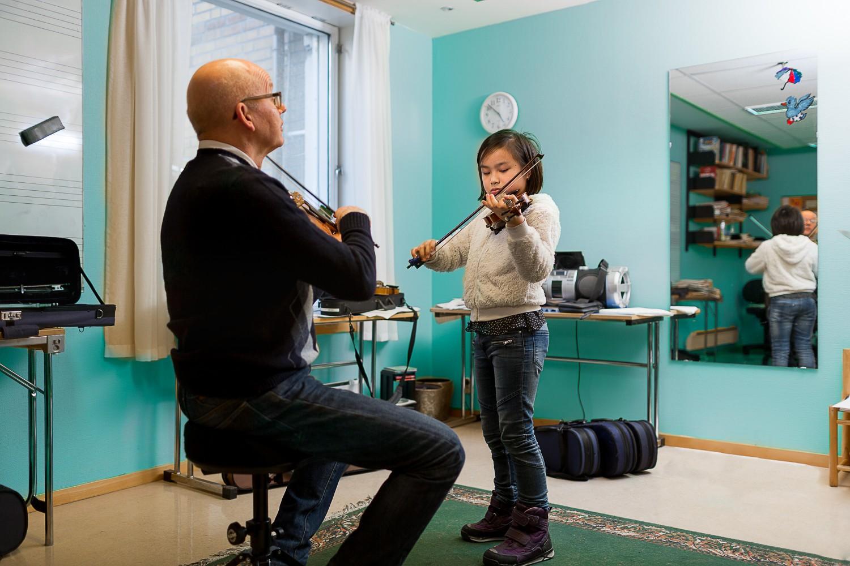 En elev, og en lærer som øver fiolin. Foto.