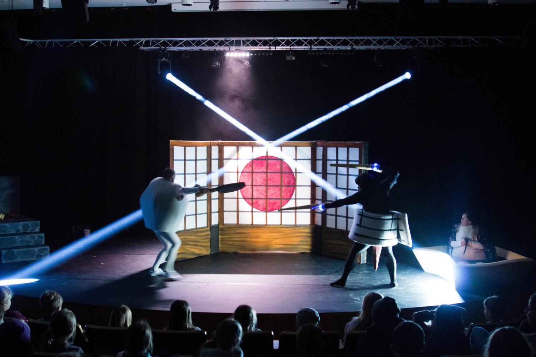 Tp personer på scenen som er i kamp, hvor den ene er kledd ut som en sushi, og den andre en kompe. Foto.