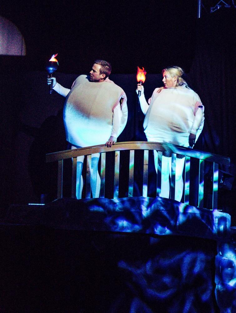 To personer på scenen som holder en fakkel hver, kledd ut som komper. Foto.