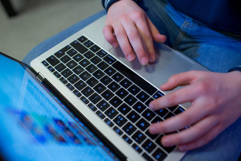 Nærbilde av en elev som produserer musikk digitalt. Foto.