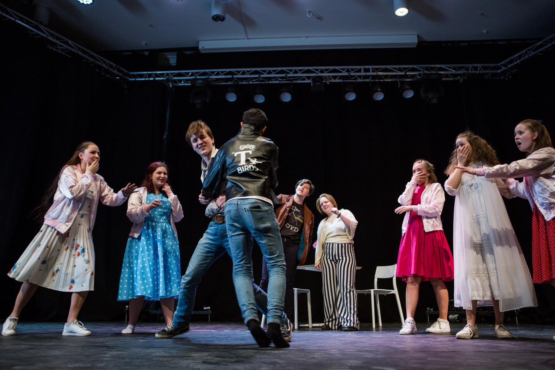 En gruppe elever under fremføring av musikalen fame. To karakterer er under en slåsskamp, mens resten følger med i spenning. Foto.