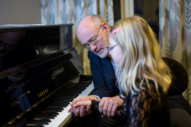 En elev som spiller piano med en hjelpende hånd fra en lærer. Foto.