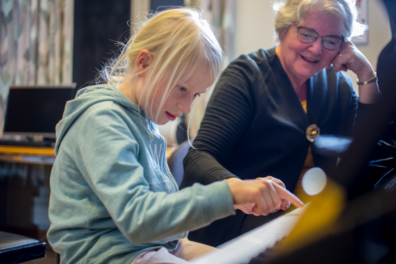 En elev som spiller piano, og en lærer som hjelper til. Foto.