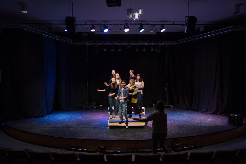 En gruppe mennesker på scenen som synger kor i lag. Foto.