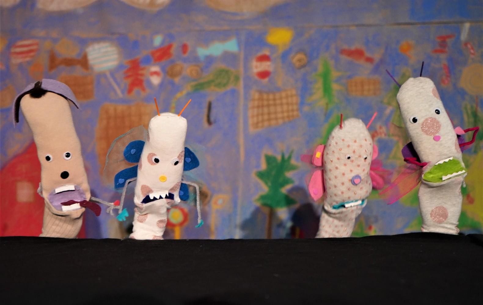 Barn viser frem sine tøydukker. Foto.
