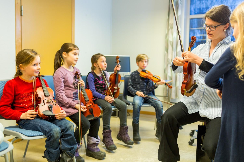 En gruppe elever som gjør seg klar for å spille fiolin, og en lærer som hjelper. Foto.
