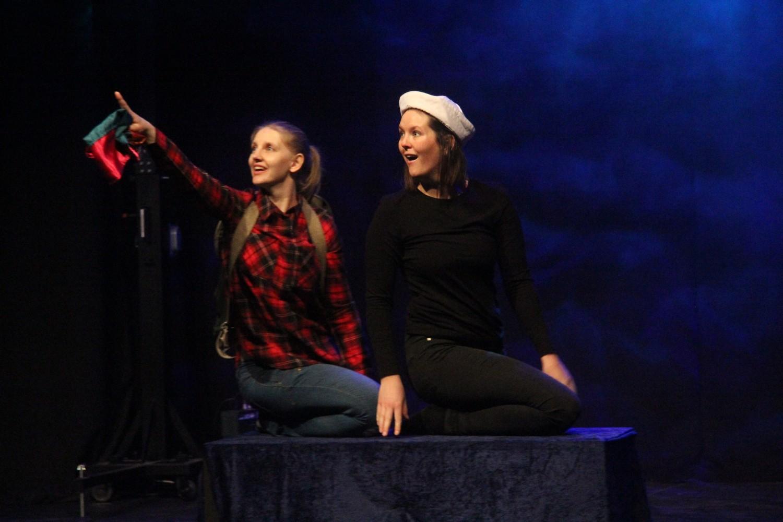 To personer på scenenen, hvor en peker mot været. Foto.