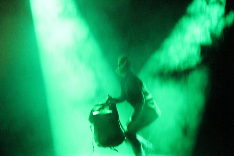 En person på scenen som holder en sekk, med en intens grønn belysning. Foto.