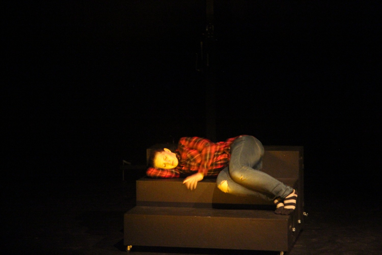 En person som ligger på scenen. Foto.