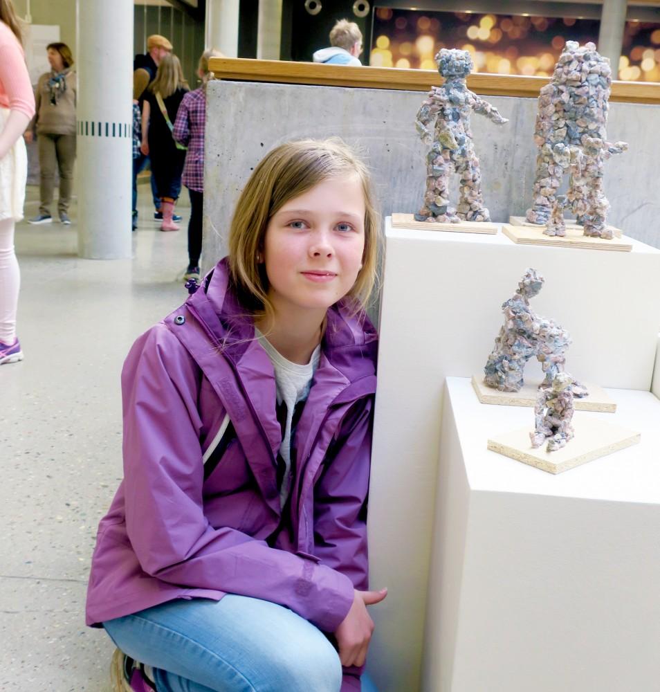 En elev ved siden av en utstilling av noen skulpturer. Foto.