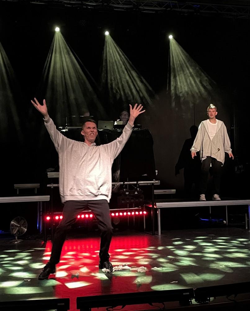 To skuespiller på en scene hvor den ene holder begge hender i luften. Foto.