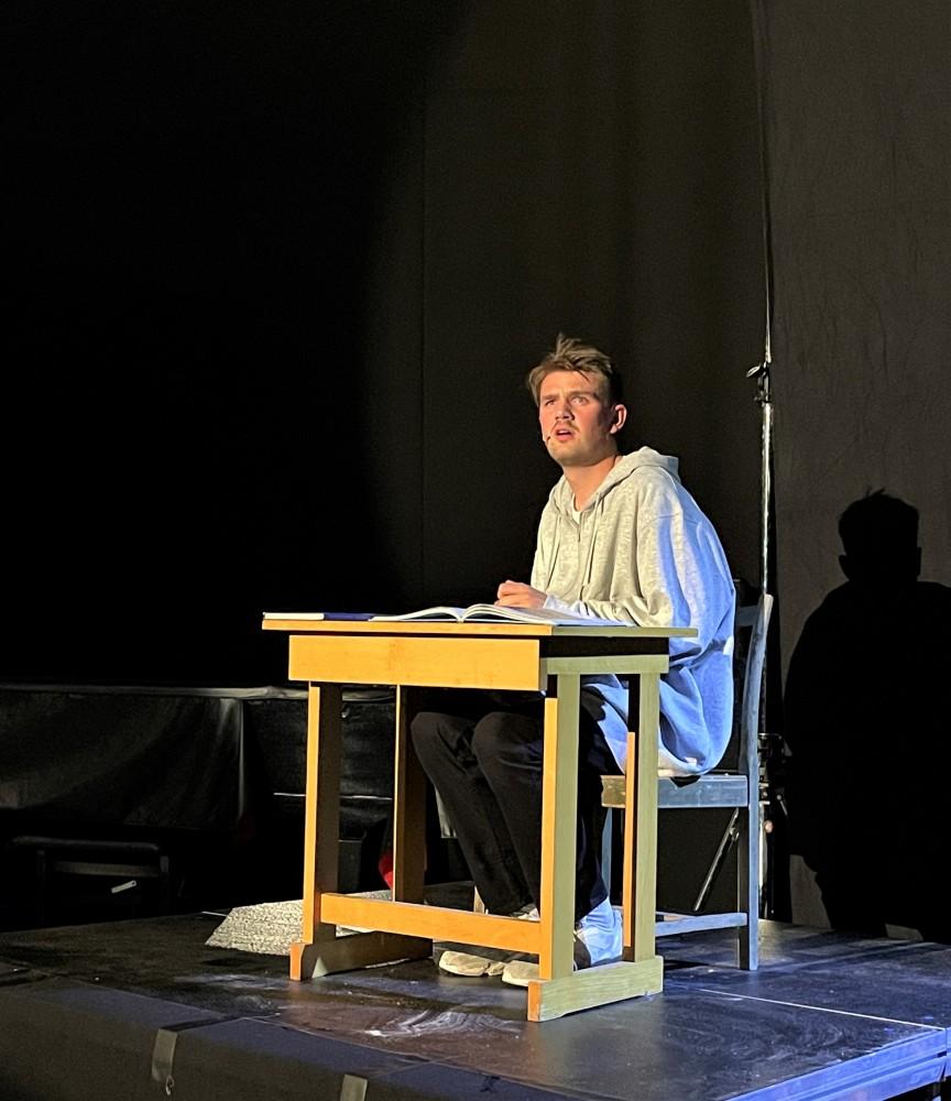 En skuespiller sitter ved en pult på scenen. Foto.